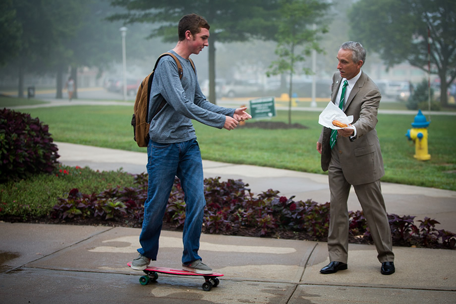 President Jasinski handing a donut to a Northwest student on the first day of class.