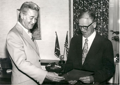 Dr. Robert Foster honors Coach Ryland的米尔纳 with an award. Milner became head coach of the Northwest football team in 1932.
