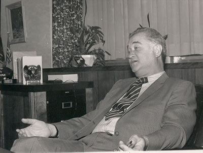 Dr. Foster sits in his office in the 管理 Building.  Dr. Foster oversaw many expansions on campus, such as the high-rise residence halls.  The Memorial Bell Tower was also the brainchild of Dr. Foster, who wanted a lasting memorial to the men and women who had served in World War II.  Dr. Foster's 钟楼 efforts resulted in the formation of the 澳门赌场app基础.