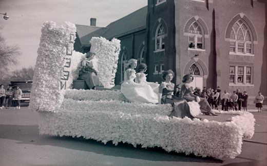 The Northwest Tower Queen, attired in her evening finery, rides on a float with her royal court during the 1962 归国 Parade.