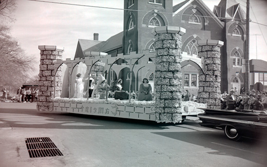 A Camelot float filled with lovely medieval-dressed Northwest students is paraded down a Maryville Street.  Camelot, due to the Kennedys and the musical, was a popular theme during the early 1960s.  Camelot, the musical about King Arthur, first appeared on Broadway in 1960.