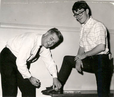 President Foster shines a student's shoes during the early 1960s during Parents' Day Activities.