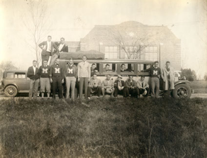 The 1931-1932 MIAA Champion Basketball Team poses outside the first gymnasium (now Martindale Hall) with their coach Henry Iba.