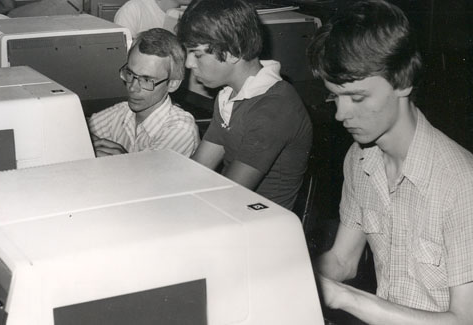 With the addition of a Computer Science degree, Northwest attracted students interested in computing and information technology.  One of the first programming classes was taught by Dr. Gary McDonald. McDonald is shown helping students in his class.