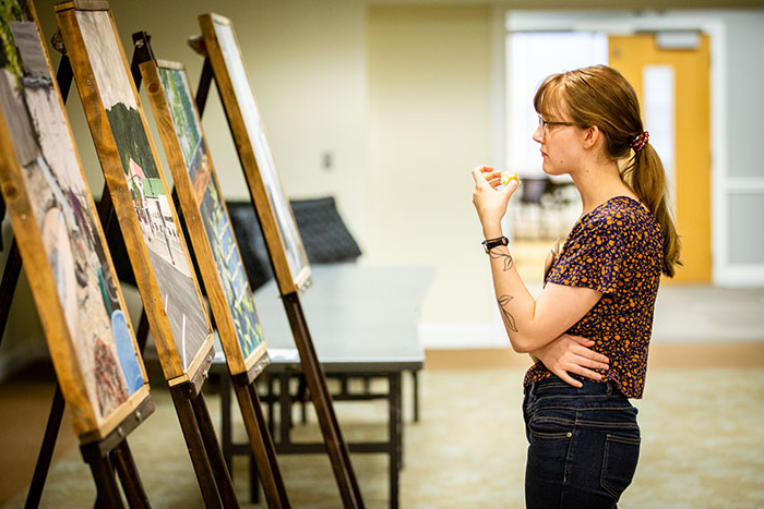 A Northwest student views a series of paintings presented during the annual Celebration of Quality on April 5. (Photo by Brandon Bland/Northwest Missouri State University)